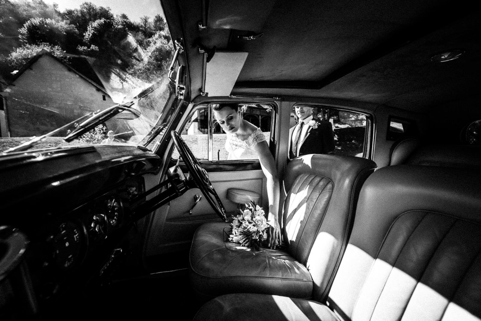 Mariée qui prends son bouquet dans sa vieille voiture